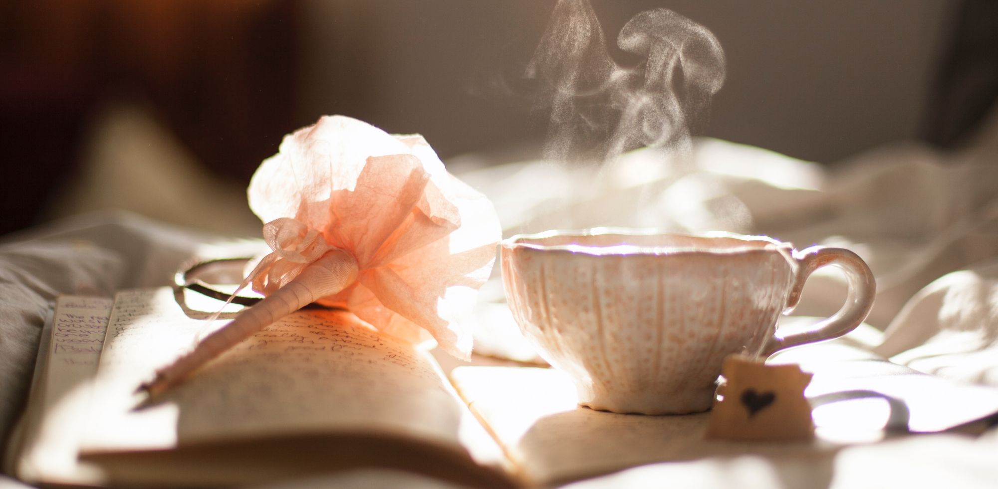 Thé fumant et crayon en forme de fleur sur un livre ouvert